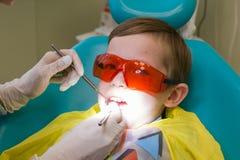 牙科的招待会 一个小男孩在长沙发和采取放置治疗 免版税库存图片