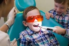 牙科的招待会 一个小男孩在长沙发放置,并且他的兄弟在他的嘴投入灯 免版税库存照片