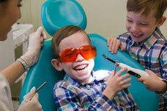 牙科的招待会 一个微笑的小男孩在停留在他旁边的长沙发和他的兄弟放置 免版税库存照片