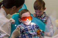 牙科的招待会 一个微笑的小男孩在长沙发放置 图库摄影