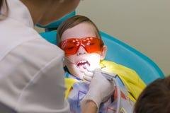 牙科的招待会 男孩采取口腔医学治疗 图库摄影