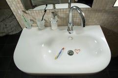 牙膏的心脏在水盆的 库存照片