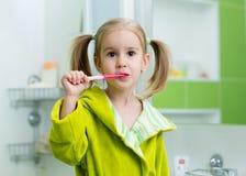 牙齿保护-清洗她的牙的儿童女孩 免版税库存图片