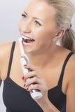 牙齿健康:刷她的牙的白种人白肤金发的妇女通过使用 免版税库存图片