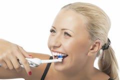 牙齿健康:刷她的牙的白种人白肤金发的妇女通过使用 免版税库存照片