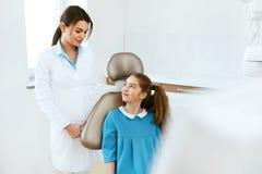 牙齿健康 牙医和愉快的女孩在牙科办公室 库存照片