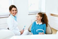 牙齿健康 牙医和愉快的女孩在牙科办公室 免版税图库摄影