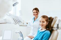 牙齿健康 牙医和愉快的女孩在牙科办公室 图库摄影