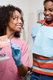 牙齿护士显示男孩如何适当地清洗牙 免版税库存图片