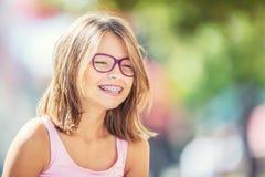 戴牙齿括号和眼镜的愉快的微笑的女孩 年轻逗人喜爱的白种人白肤金发的女孩佩带的牙括号和玻璃 库存图片