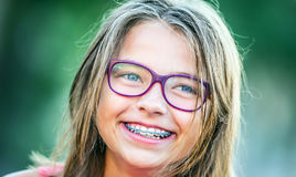 戴牙齿括号和眼镜的愉快的微笑的女孩 年轻逗人喜爱的白种人白肤金发的女孩佩带的牙括号和玻璃 免版税库存照片