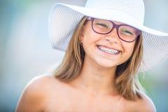 戴牙齿括号和眼镜的愉快的微笑的女孩 年轻逗人喜爱的白种人白肤金发的女孩佩带的牙括号和玻璃 库存照片