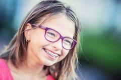 戴牙齿括号和眼镜的愉快的微笑的女孩 年轻逗人喜爱的白种人白肤金发的女孩佩带的牙括号和玻璃 免版税图库摄影