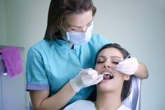 牙齿核对的美丽的少妇参观的牙医 免版税图库摄影