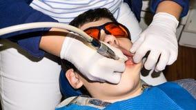 牙齿治疗的男孩 大括号装箱的 胳膊关心健康查出滞后 库存照片