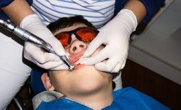 牙齿治疗的自我中心男孩 大括号装箱的 胳膊关心健康查出滞后 免版税库存照片