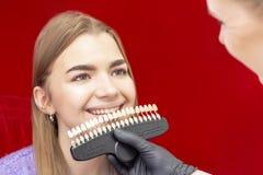 牙齿美白做法女孩牙齿美白的招待会牙医医生拾起牙的颜色 免版税库存图片