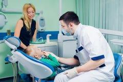 年轻牙医与儿童患者一起使用在一家现代医院 图库摄影