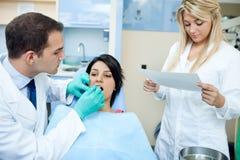 牙医和一位护士有患者的在办公室 免版税图库摄影