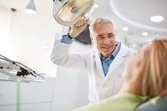 牙医在开始工作前调整探照灯 免版税图库摄影