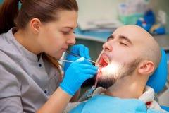 牙医审查在牙医椅子的患者牙在b下 免版税库存图片