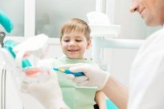 牙医教小男孩怎么对清洗的牙 图库摄影