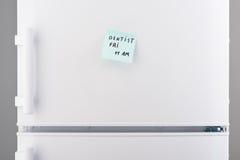 牙医星期五上午11点在蓝色便条的在白色冰箱 图库摄影
