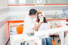 牙医医生在牙齿办公室对待牙耐心女孩 免版税库存图片