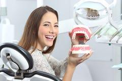 牙医耐心微笑与塑料假牙 库存照片