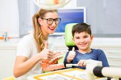 牙医解释的男孩清洁牙 免版税图库摄影