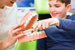 牙医解释的男孩清洁牙 免版税库存照片