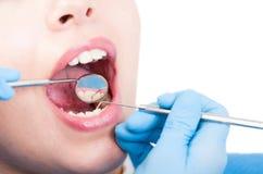 牙医调查与牙齿镜子的女性的嘴 库存图片