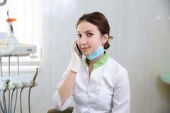 牙医谈话在电话在牙齿办公室 概念的健康 免版税图库摄影