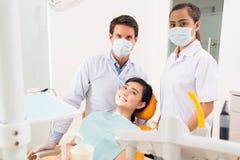 牙医,辅助和微笑的患者 库存照片