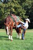 牛仔他的马挂接 免版税图库摄影