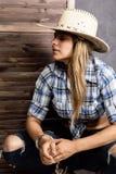 牛仔女孩或俏丽的妇女时髦的帽子和蓝色拿着枪和老手提箱的格子花呢上衣的 库存照片