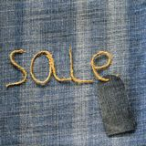 牛仔布与麻线题字销售的织品背景在我的 库存照片