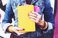 牛仔布夹克的女孩有五颜六色的习字簿的 库存照片