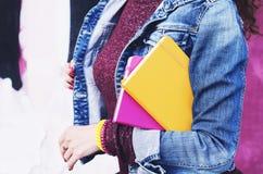 牛仔布夹克的女孩有五颜六色的日志的在她的手上 免版税库存照片