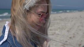 牛仔布夹克的年轻白肤金发的妇女在海和海滩的背景使用一个智能手机振翼她的头发  股票录像