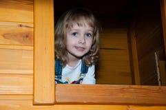 牛仔布总体的一个女孩充当操场的一个木比赛房子在赌博中心 库存照片