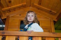 牛仔布总体的一个女孩充当操场的一个木比赛房子在赌博中心 免版税图库摄影