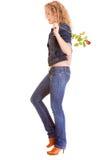 牛仔布时尚。蓝色牛仔裤的全长白肤金发的女孩有红色玫瑰的 图库摄影