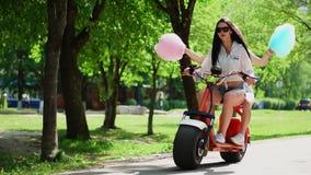 牛仔布短裤的两个美丽的女孩在公园乘坐在一辆电滑行车在夏天 股票录像