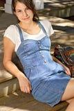 牛仔布礼服的微笑的十几岁的女孩 库存照片