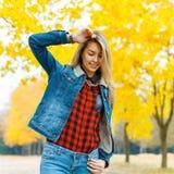 牛仔布衣物的少妇有秋叶的在手中和fal 免版税库存照片