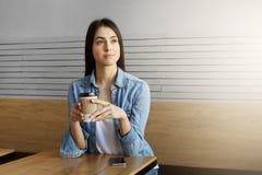 牛仔布衬衣和白色T恤杉的美丽的年轻深色头发的女孩喝咖啡,看在旁边与轻松的表示 免版税库存照片