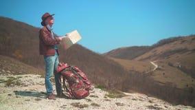 牛仔帽、皮夹克、蓝色牛仔裤和玻璃的一个人在山站立,考虑旅客地图 股票录像