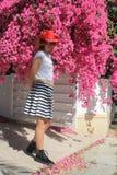 牛仔帽的女孩在桃红色花旁边 免版税图库摄影