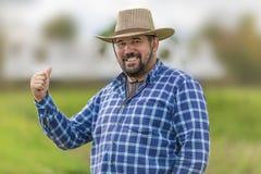 牛仔帽的有胡子的人微笑和显示赞许,对此的蓝色检查了衬衣和他` s身分 免版税库存照片